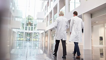 From the rear, two doctors walk into the building towards the outlet