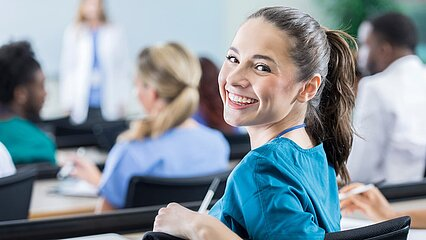 Prospective doctor smiles and turns back into camera at lecture
